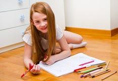 Ein kleines Mädchen zeichnet während Lügen auf Boden lizenzfreie stockfotografie