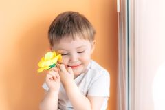 Ein kleines Mannkinderkleinkind, das eine gelbe Rose halten und ein schüchtern auf orange Hintergrund lizenzfreie stockbilder