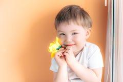 Ein kleines Mannkinderkleinkind, das eine gelbe Rose halten und ein schüchtern auf orange Hintergrund stockfotografie