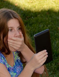 Ein kleines Mädchen erschrak von, was sie online sieht Stockfotografie
