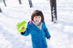 Mädchen, das glücklich im Schnee spielt Stockbilder