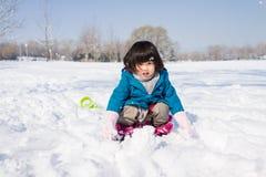 Mädchen, das glücklich im Schnee spielt Lizenzfreie Stockfotos