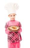 Ein kleines Mädchen hält eine Platte der Torte an Stockfotografie
