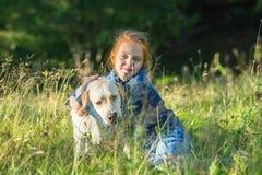 Ein kleines Mädchen liegt im Gras mit dem Hund nave Stockbilder