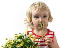 Ein kleines Mädchen mit einem Blumenstrauß der Blumen Lizenzfreies Stockfoto