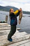Ein kleines Mädchen in Norwegen hat einen großen Fisch in der Hand Lizenzfreie Stockfotos