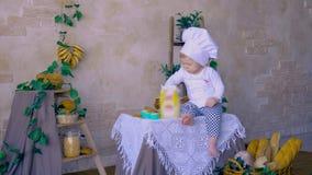 Ein kleines nettes Babykind mit dem Kochen von den Hauben, die mit Weizenmehl spielen stock video footage