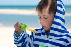 Ein kleines nettes Kind in einer gestreiften Robe brennt Seifenblasen vor dem hintergrund des Meeres und des gewaschenen Spuckens Stockbilder