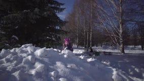Ein kleines nettes Mädchen, das mit Schnee im Winterpark spielt stock footage