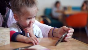 Ein kleines nettes Mädchen des europäischen Auftrittes sitzt auf den Händen ihrer Mutter an einem Tisch ein Video auf ihrem Körpe stock footage