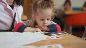 Ein kleines nettes Mädchen des europäischen Auftrittes sitzt in ihren Mutterarmen an einem Tisch ein Video aufpassend auf einem S stock video footage