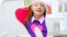Ein kleines nettes Mädchen mit dem roten Haar bewundert ihre gesunden Zähne im Spiegel, der im zahnmedizinischen Stuhl sitzt stock footage