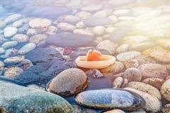 Ein kleines Plastikschiff auf den Wellen über den runden Steinen Das Konzept der Freiheit, Reise Stockbilder