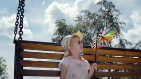 Ein kleines süßes Mädchen in der Sonnenbrille schwingt auf einem ständigen Schwanken an einem sonnigen warmen Tag stock video