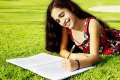 Ein kleines schönes Mädchen zeichnet Herz im Park Stockfoto