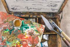 Ein kleines sketchbox, eine Palette, eine Bürste, ein Palettenmesser für Malereien lizenzfreies stockfoto