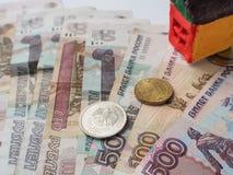 Ein kleines Spielzeughauskonzept in den russischen Rubeln Das Konzept von Einsparungen und von Aspirationen lizenzfreie stockbilder