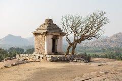 Ein kleines Steingebäude mit einem Baum Stockfoto