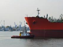 Ein kleines Versuchsschiff führt ein großes rotes Frachtschiff am Seehafen an einem windstillen Herbsttag lizenzfreies stockbild