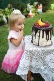 Ein kleines weiß-haariges Mädchen von zwei Jahren versucht einen Geburtstagskuchen Kleines Mädchen, das zweiten Geburtstag feiert Lizenzfreies Stockfoto