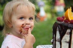 Ein kleines weiß-haariges Mädchen von zwei Jahren versucht einen Geburtstagskuchen Kleines Mädchen, das zweiten Geburtstag feiert Lizenzfreie Stockfotografie