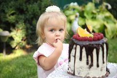 Ein kleines weiß-haariges Mädchen von zwei Jahren versucht einen Geburtstagskuchen Kleines Mädchen, das zweiten Geburtstag feiert Lizenzfreies Stockbild