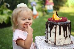 Ein kleines weiß-haariges Mädchen von zwei Jahren versucht einen Geburtstagskuchen Kleines Mädchen, das zweiten Geburtstag feiert Stockfoto