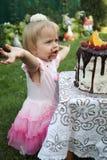 Ein kleines weiß-haariges Mädchen von zwei Jahren versucht einen Geburtstagskuchen Kleines Mädchen, das zweiten Geburtstag feiert Stockfotos