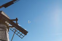 Ein kleines weißes Flugzeug, das über die alte hölzerne Mühle fliegt Lizenzfreies Stockbild