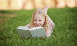 Ein Kleinkind, das auf dem Gras liest ein Buch liegt Lizenzfreie Stockfotografie