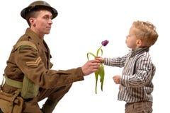 Ein Kleinkind gibt einem britischen Soldaten eine Blume Lizenzfreie Stockfotos