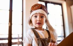 Ein Kleinkindjunge mit dem Kartonflugzeug, das zuhause zu Hause, fliegendes Konzept spielt lizenzfreies stockfoto