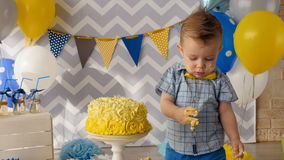 Ein Kleinkindjunge mit Kuchenstellen auf seinem Gesicht stock video