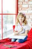 Ein Kleinkindmädchen sitzt auf dem Fensterbrett und denkt auffassung lizenzfreie stockfotografie