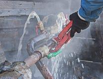 Ein Klempner repariert ein Wasserleck auf einer Wasserleitung Stockbilder