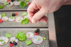 Ein Koch fügt eine Klemme Salz einem künstlerischen Überzug des Mikrogrün- und Rettichsalats hinzu lizenzfreie stockfotos
