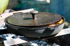 Ein Kochen im Freien mit Roheisenbratpfanne lizenzfreie stockfotografie