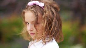 Ein koketter Blick von am Boden Süßes gelocktes braunäugiges Mädchen untersucht die Kamera kokett, sie hat ein Rosa stock video