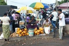 Ein Kokosnussverkäufer unter dem Chaos des Negombo-Fischmarktes Sri Lanka stockfotos
