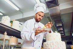 Ein Konditor mit Nachtisch in seinen Händen lizenzfreies stockfoto