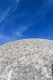 Ein konkretes Gebäude, das wie die kugelförmige Oberfläche der Mondaufstiege über dem hellen blauen Himmel mit Wolken aussieht Stockbilder