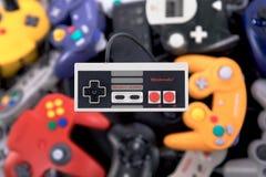 Ein Kontrolleur Hovering Nintendos NES über einem Stapel von Retro- Videospiel-Prüfern stockfoto