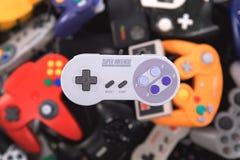 Ein Kontrolleur Hovering Nintendos SNES über einem Stapel von Retro- Videospiel-Prüfern lizenzfreie stockfotografie