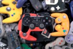 Ein Kontrolleur Hovering Sony Playstations 2 über einem Stapel von Retro- Videospiel-Prüfern stockfoto