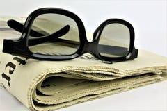Ein Konzept Bild einer Zeitung mit Gläsern lizenzfreies stockbild