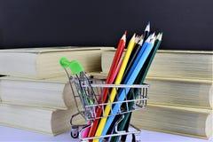 Ein Konzept Bild einiger bunter Bleistifte mit etwas Büchern und Kopienraum Lizenzfreies Stockfoto