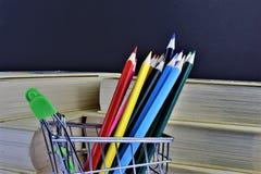 Ein Konzept Bild einiger bunter Bleistifte mit etwas Büchern und Kopienraum Lizenzfreies Stockbild