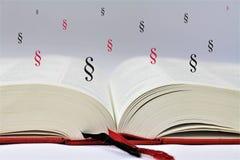 Ein Konzeptbild eines offenen Buches mit abstrakten Paragraphen Lizenzfreies Stockbild