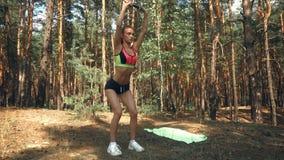 Ein kräftiger Athlet steht im Wald und macht Übung auf Ihrer Rückseite mit Dumbells stock footage