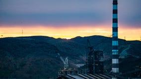 Ein Kran und eine Raffinerie, die bei Sonnenuntergang im Berg Isa, Queensland funktionieren stockbilder